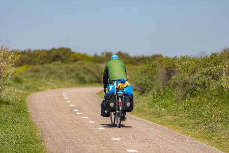 Cyclist on a bike path in the dunes of Noordwijk in Holland.