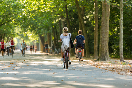 A blond girl and boy biking in the Vondelpark in Amsterdam in the Netherlands.