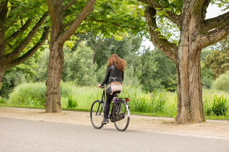 Girl biking on a omabike in the Amsterdam Vondelpark in the Netherlands.