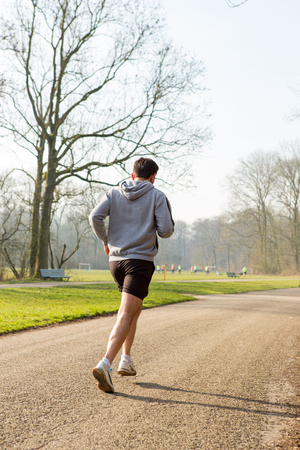 Man running on a asphalt path in the Amsterdamse Bos. Stockfoto