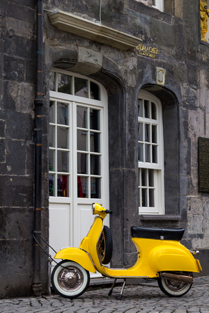 A yellow classic scooter locked in a historic house in the center of the German city of Essen. Stockfoto
