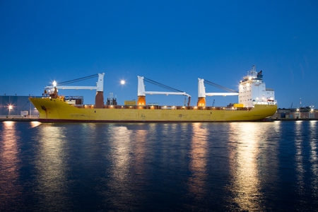 Big containership with cranes in the evening in the Amsterdam Coenhaven harbour in the Netherlands. Stockfoto
