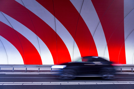 A black car driving fast in a tunnel with red dynamic stripes on the wall in the Dutch village Badhoevedorp.