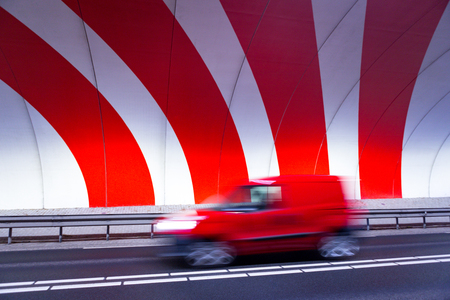 A red car driving fast in a tunnel with red dynamic stripes on the wall.