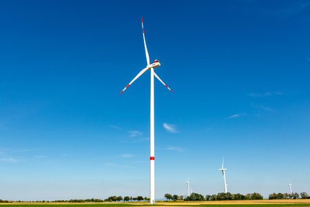Beautiful greenyellow landscape with white wind turbines with red stripes generating electricity on a bright blue cloudy sky.
