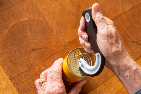 Man opening a tin can with a special opener while taking occupational therapy Stock fotó