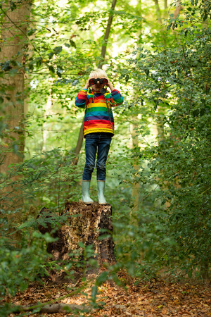 Boy looking around in the forest looking with a binocular in Park Landgoed Huys te Warmont in the Netherlands. Stockfoto