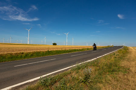 A motorcyclist in an agricultural landscape with wind turbines in the background Stockfoto