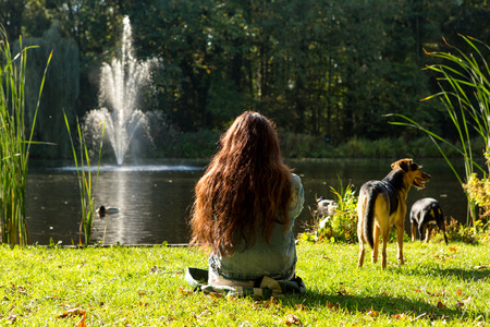 A girl relaxing in the grass on the side of a pond with 2 dogs in the city of Leiden in the Netherlands.