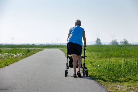 An older woman with a walker to help her to walk outside in nature. Leiderdorp the Netherlands.
