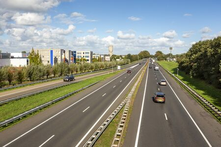 Cars driving on the A44 highway in the village of Sassenheim in the Netherlands. Фото со стока