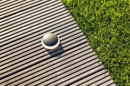 Round black outdoor lighting on a light brown jetty with adjacent fresh green grass. Stok Fotoğraf