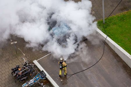 A firefighter creates a lot of smoke and steam when putting out a car in the driveway of a parking garage on Fregelaan in Amsterdam the Netherlands.