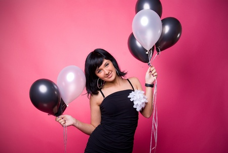 Photo of a young girl with a black and white balloons on a pink background Archivio Fotografico
