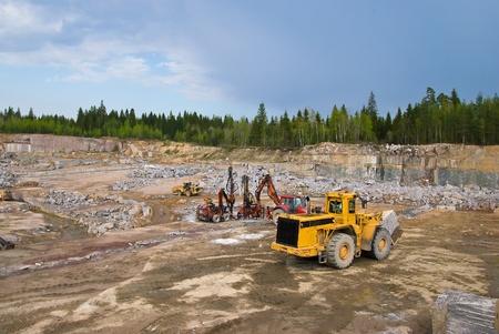 Production of stone in granite quarry. Mining machines photo