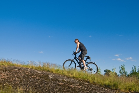 Young man on a mountain bike climbing the hill Archivio Fotografico