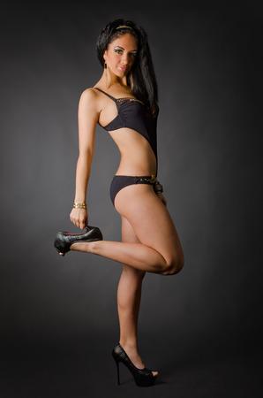 Beautiful female model posing in black swimsuit photo