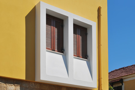 Greek window with wooden shutters. Brown wooden shutters with jalousie on the facade of a house in the old Greek city. Stock Photo