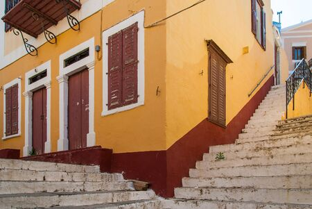 Symi Island. Corner of an old house with steps going in opposite directions. Old house on narrow street Symi