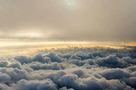 Clouds and sky as seen through window of an aircraft. Flying above the clouds