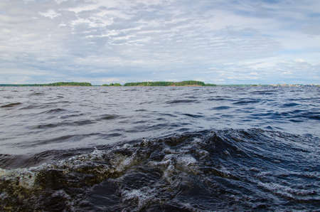 Waves from sailboat on Baltic sea. Seascape with islands on Baltic sea