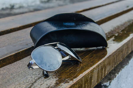 Aviator sunglasses with a cover on a rain-wet bench