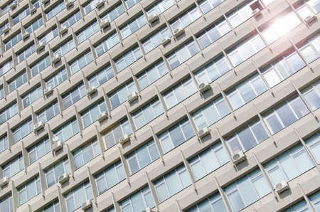 The texture of the facade of a soviet building with a lot of windows and air conditioners