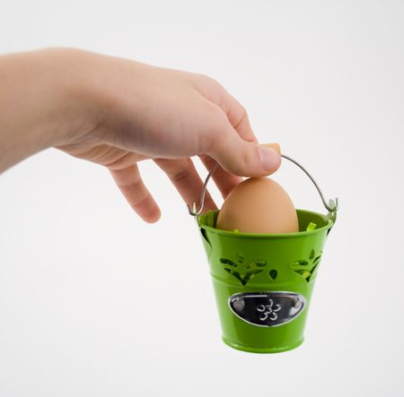 Hand holding green basket with egg, on white background. photo