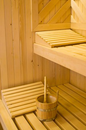 Bucket for water and two pillows on bench in Finnish sauna.