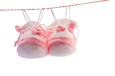 Pair of babys slippers hanging on a rope. Including copy space. Stock Photo