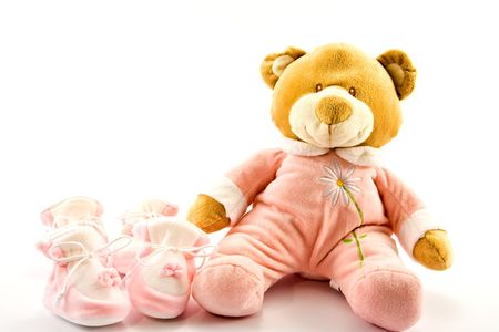 Two pairs of babys slippers and teddy bear