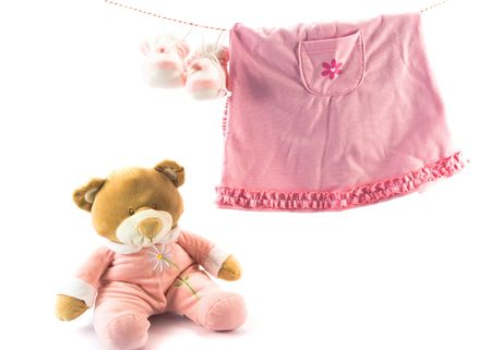 Two pairs of babys slippers and teddy bear. Copy space