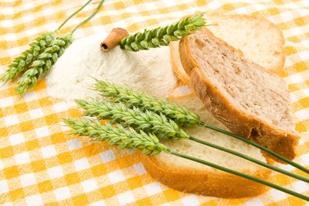 Bread, flour and green wheat on table cover. Stock Photo
