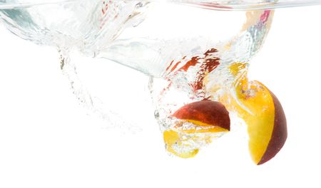 Splash of peach slices in the water. Stock Photo