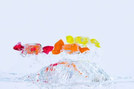 Splash of colorful fruit candies in the water with blue tint. Stock Photo - 3248585