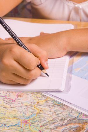 dopisní papír: Girl doing her homework by writing in notebook.