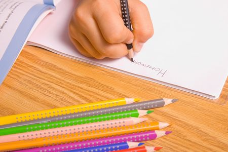 children writing: Girl doing her homework by writing in notebook.