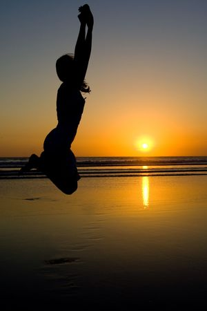 Woman jumping on the beach at sunset. photo