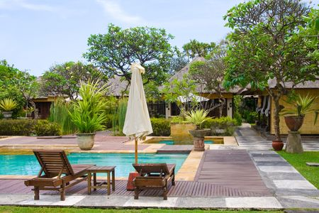 Two chairs and umbrella by the swimming pool