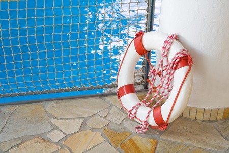 White life buoy on floor by swimming pool