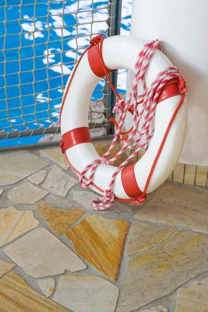 White life buoy on floor by swimming pool photo