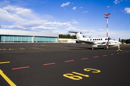 Small airplane on runway with hangar in background. photo