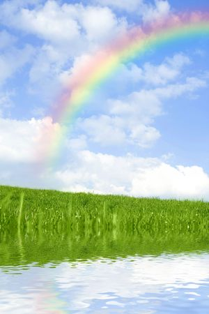 Beautiful green grass against blue sky and rainbow, with water reflection.