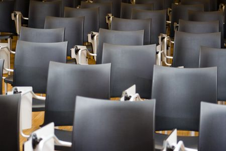 Empty black chairs in conference room. Shallow depth of field. Stock Photo