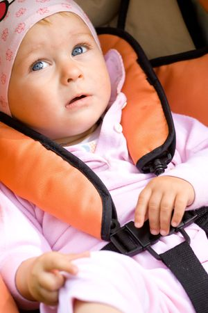 Cute girl sitting in baby carriage photo