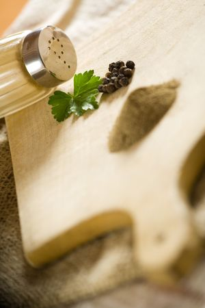 pepperbox: Black pepper seeds - whole and powder on wooden kitchen surface.