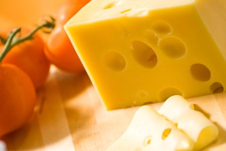 Delicious cheese on wooden desk with tomato in background Stock Photo