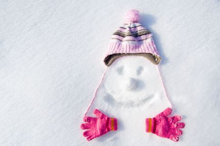 Face drawn in snow with cap, gloves and snowball. photo