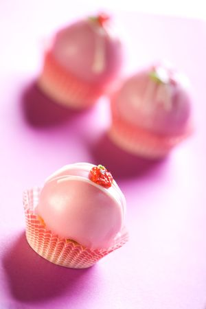 Delicious pink cupcakes on purple background. Shallow depth of field. Stock Photo - 6534367