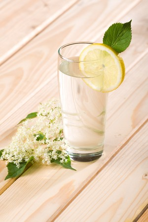 Healthy elder flower juice with lemon on wooden background. photo